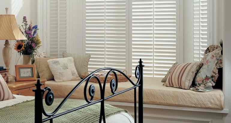 Polywood shutters in a white bedroom bay window.