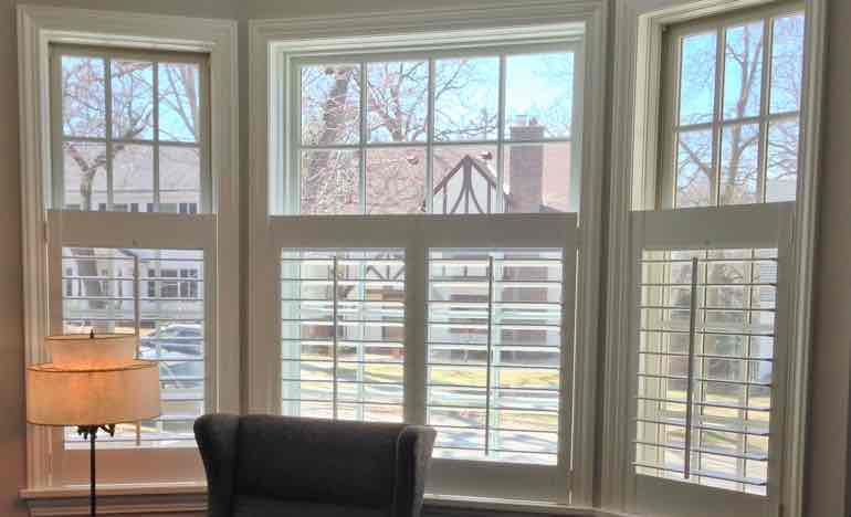 Bottom half plantation shutters in family room bay window.