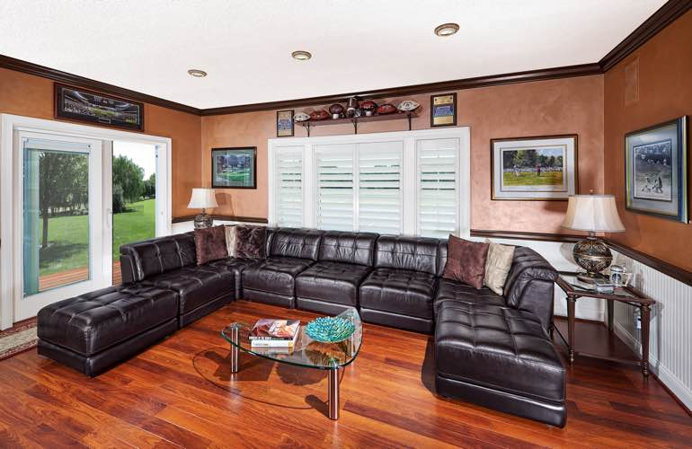 Indianapolis basement den with glass doors and shutters on windows.