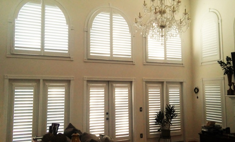 Family room in two-story Indianapolis house with plantation shutters on high windows.