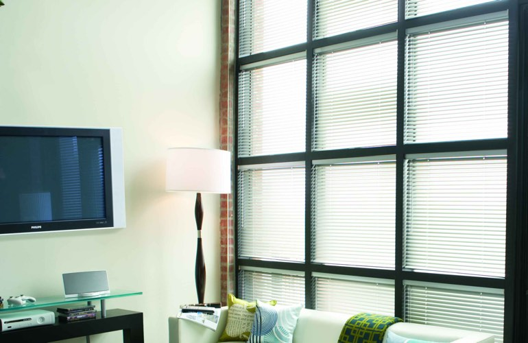 Blinds covering large window that's divided into square panes