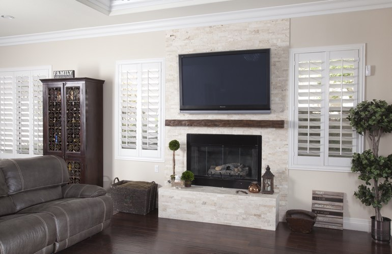 White plantation shutters in a Indianapolis living room with dark hardwood floors.