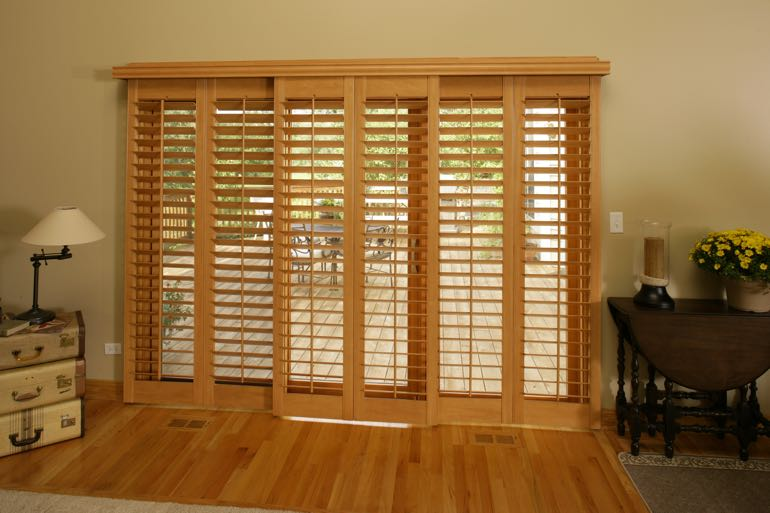 plantation shutters on sliding door going to back porch.