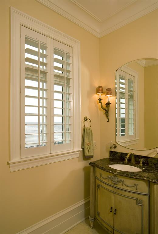 White shutters in a light bathroom outlooking the ocean