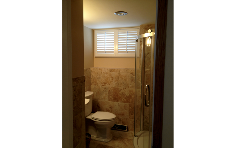 Basement bathroom window covered in white plantation shutters