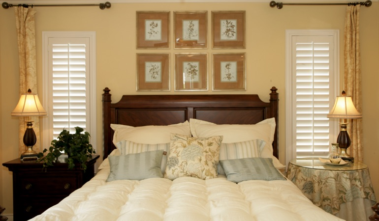 Bedroom with two tall plantation shutters on either side of bed in Indianapolis