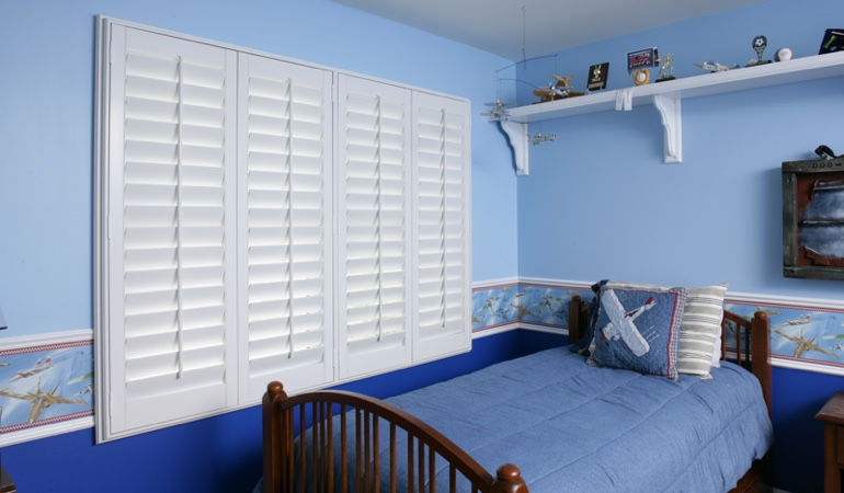 Blue kids bedroom with white plantation shutters in Indianapolis
